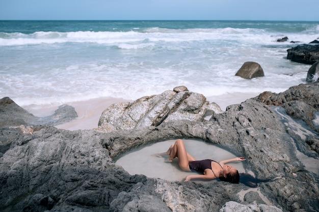 Uma mulher sexy do viajante descansando ilha tropical com praia de areia branca paradisíaca e águas turquesas e pedras de granito.