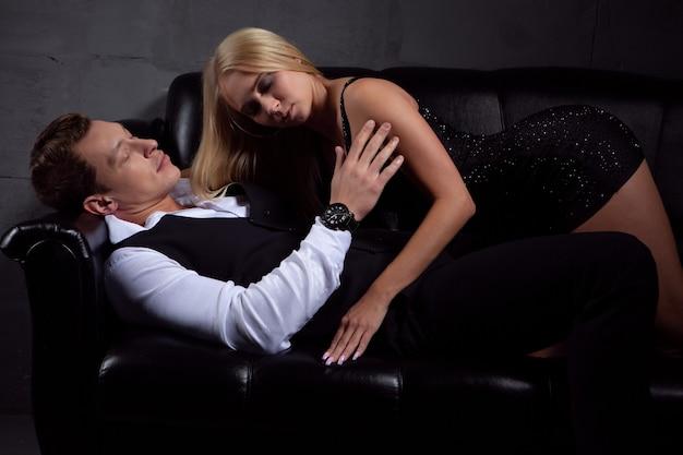 Uma mulher sexy em um vestido preto beija um homem lindo deitado no sofá