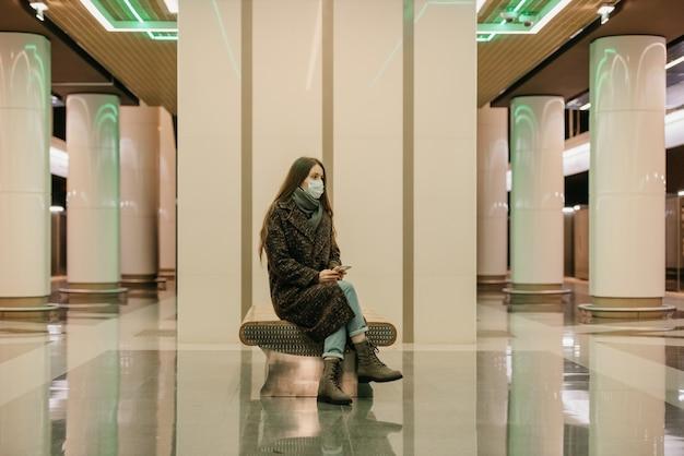 Uma mulher solitária com uma máscara médica para evitar a propagação do coronavírus está sentada com um smartphone na plataforma do metrô. uma garota com máscara cirúrgica mantém distância social no metrô.