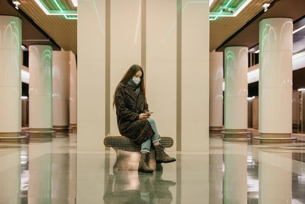 Uma mulher solitária com uma máscara médica para evitar a propagação do coronavírus está sentada usando um smartphone na plataforma do metrô. uma garota com máscara cirúrgica mantém distância social no metrô.
