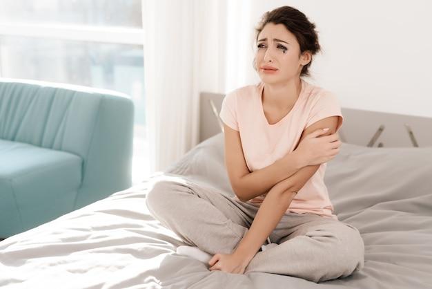 Uma mulher solitária está chorando sozinha, seu rímel fluiu.