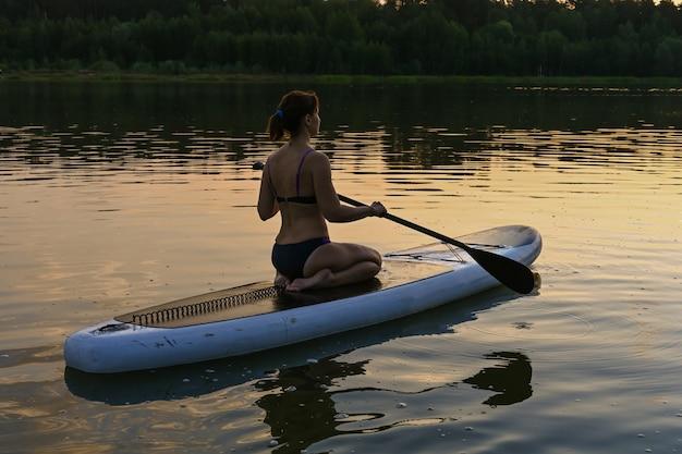 Uma mulher solitária monta um sup board em um lago rodeado por grama e densa floresta verde ao pôr do sol. lago lebyazhye, kazan.