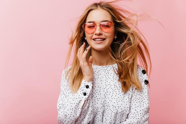 Uma mulher sonhadora de cabelos compridos e óculos de sol tem um bom dia. retrato interior de mulher romântica elegante blusa elegante.