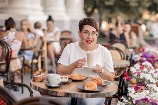 Uma mulher sorri e bebe café e bolos em um café europeu de rua