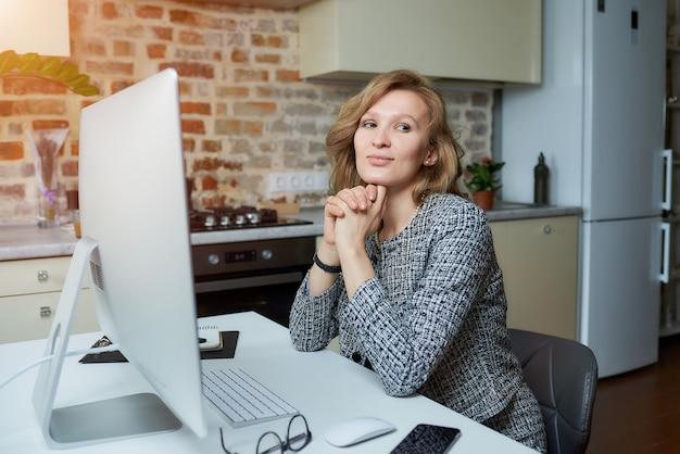 Uma mulher sorri e trabalha remotamente em um computador desktop em seu estúdio. uma senhora senta os braços cruzados durante uma videoconferência em casa.
