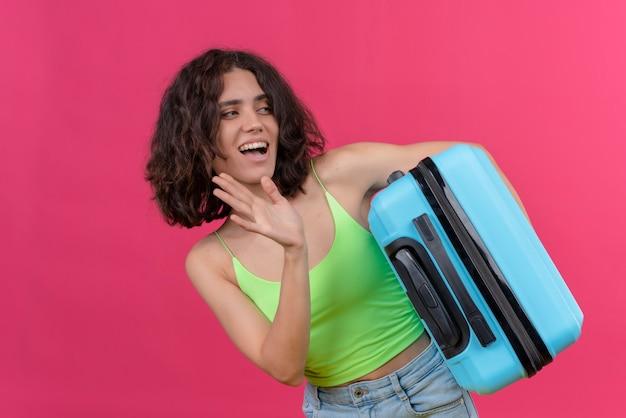 Uma mulher sorridente, atraente e adorável com cabelo curto, usando uma blusa verde cortada se despedindo segurando uma mala azul