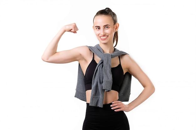 Uma mulher sorridente de fitness em um agasalho mostra seu bíceps.