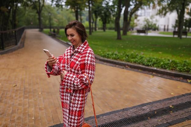 Uma mulher sorridente de meia-idade, vestindo roupas de outono.