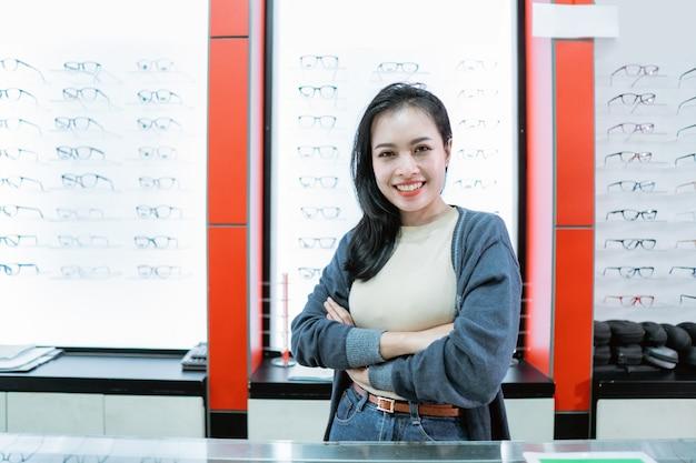 Uma mulher sorridente está em uma clínica de olhos com uma vitrine de óculos na parede
