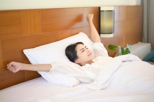 Uma mulher sorridente, esticando as mãos depois de acordar de manhã em casa.