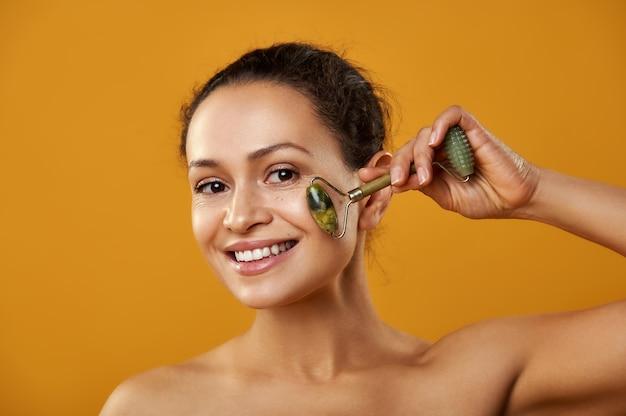 Uma mulher sorridente massageando a pele do rosto com um rolo de jade isolado em um fundo amarelo