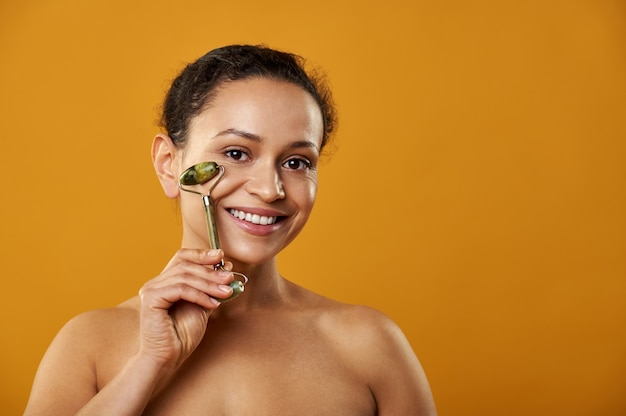 Uma mulher sorridente massageando o rosto com um rolo de jade isolado em um fundo amarelo