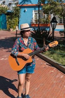 Uma mulher sorridente que toca violão enquanto caminha no parque
