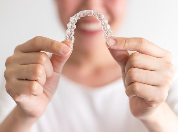 Uma mulher sorridente segurando invisalign ou aparelho invisível, equipamentos ortodônticos