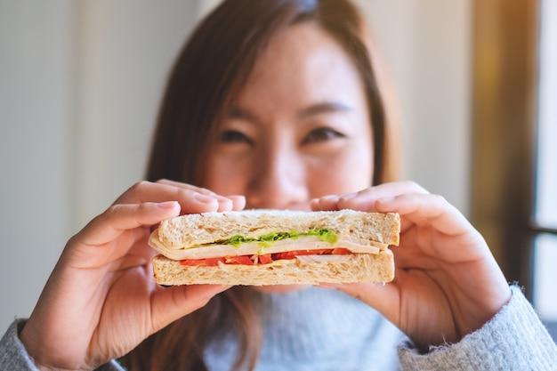 Uma mulher sorridente segurando um pedaço de sanduíche de trigo integral cobrindo o rosto