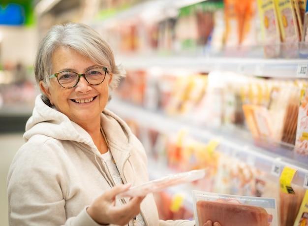 Uma mulher sorridente sênior no supermercado escolhe qual presunto comprar.