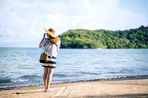 Uma mulher sozinha andando na praia, marca de koh tailândia