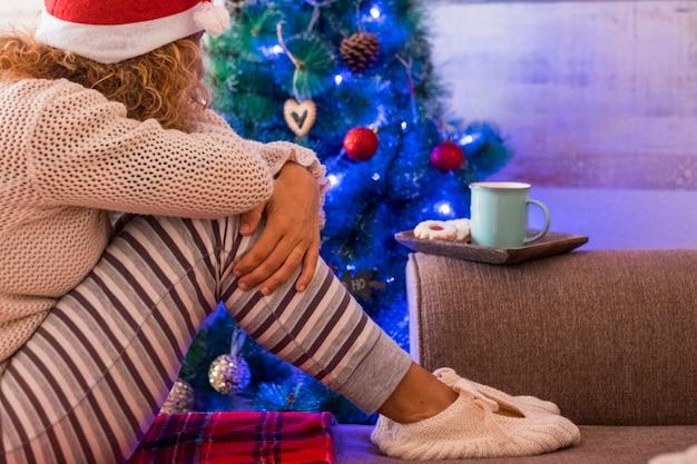 Uma mulher sozinha em casa sentada no sofá ao lado da árvore de natal comemorando o natal em casa - estilo de vida inipendente