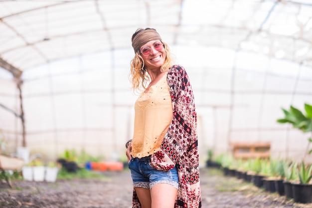 Uma mulher sozinha em sua fazenda com muitas plantas no fundo e com mais alguém