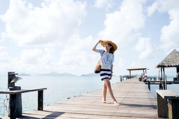 Uma mulher sozinha postando na ponte de madeira - marca de koh, tailândia