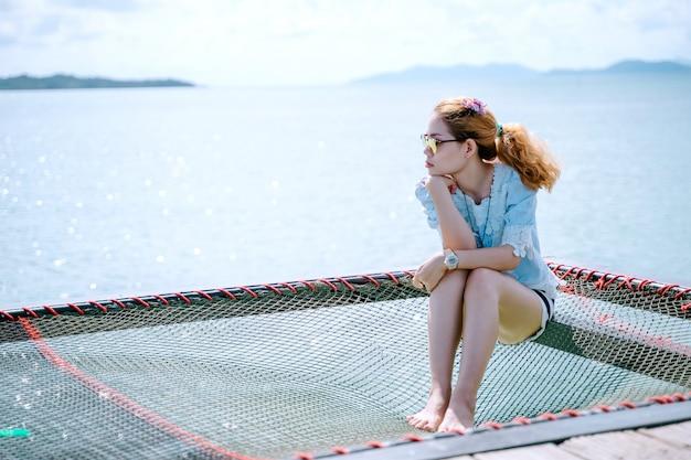 Uma mulher sozinha relaxando na praia hammock - koh mark, tailândia
