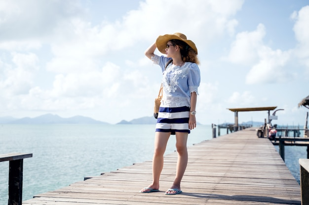 Uma mulher sozinha relaxante na ponte de madeira - marca de koh, tailândia