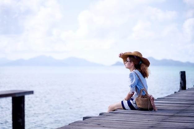 Uma mulher sozinha sentada na ponte de madeira - marca de koh, tailândia