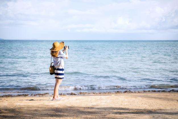 Uma mulher sozinha tirando uma foto na praia, marca de koh tailândia