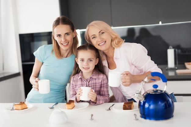 Uma mulher, sua mãe e filha estão tomando chá.
