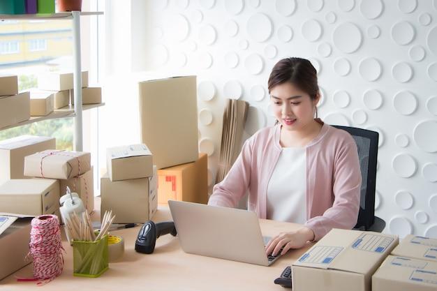 Uma mulher tailandesa asiática está sentada em um laptop imprimindo um documento em uma sala de trabalho