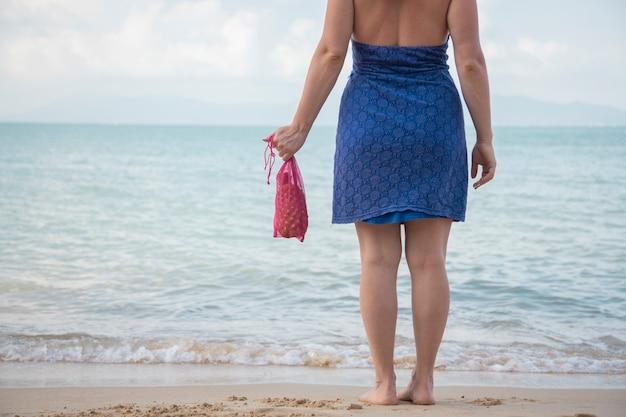 Uma mulher tem na mão uma sacola de compras de malha e fica à beira-mar em uma praia arenosa. conceito de ecologia. consumo consciente