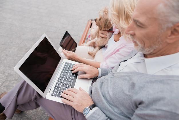 Uma mulher tem um cachorro, um homem está segurando um laptop no colo.
