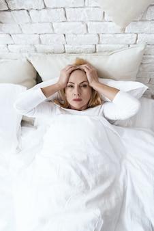 Uma mulher tem uma dor de cabeça deitada na cama.