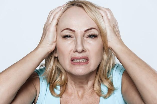 Uma mulher tem uma dor de cabeça. ela se sente mal no quarto.