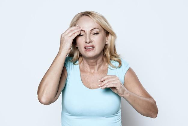 Uma mulher tem uma dor de cabeça.