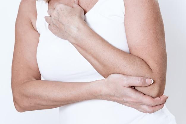 Uma mulher tem uma dor no braço. ela segura isso.