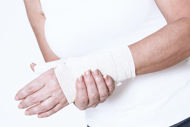 Uma mulher tem uma dor no braço.