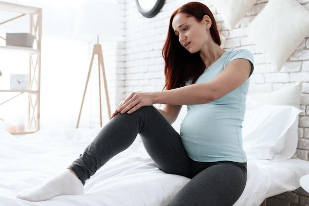 Uma mulher tem uma dor no joelho, ela está fazendo uma massagem.