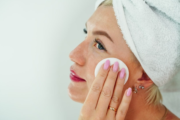 Uma mulher tira a maquiagem com um guardanapo no banheiro, enxuga o rosto com um pano de limpeza de algodão e ...