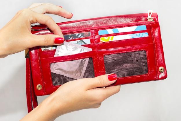 Uma mulher tira um preservativo de sua bolsa