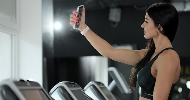 Uma mulher tira uma selfie na esteira da academia. garota atraente correndo na esteira e tomando selfie com smartphone no ginásio.