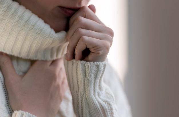 Uma mulher tocando a garganta com tosse e feridas. mulher doente com gripe em suéter branco em dia de inverno.