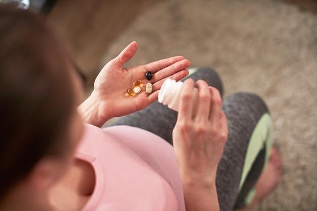 Uma mulher toma vitaminas durante a gravidez. menina grávida com um copo de água e um punhado de drogas na mão.