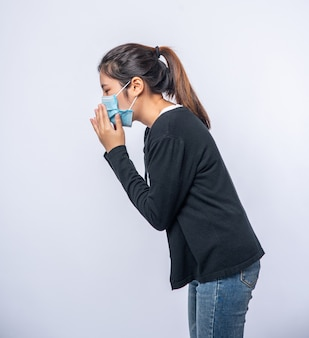 Uma mulher tossindo e cobrindo a boca com a mão