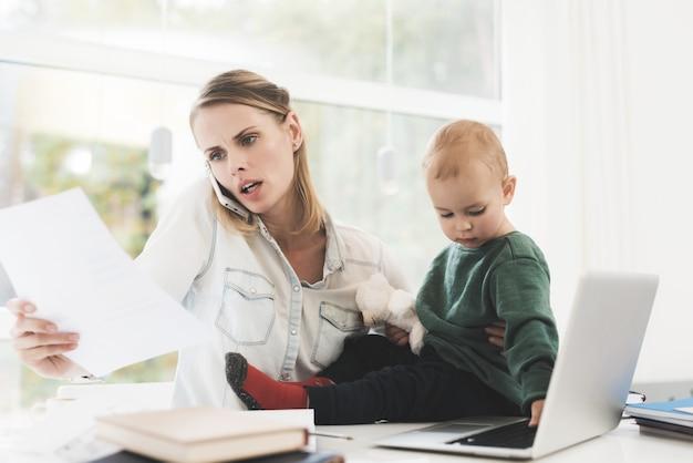 Uma mulher trabalha e cuida de uma criança ao mesmo tempo.