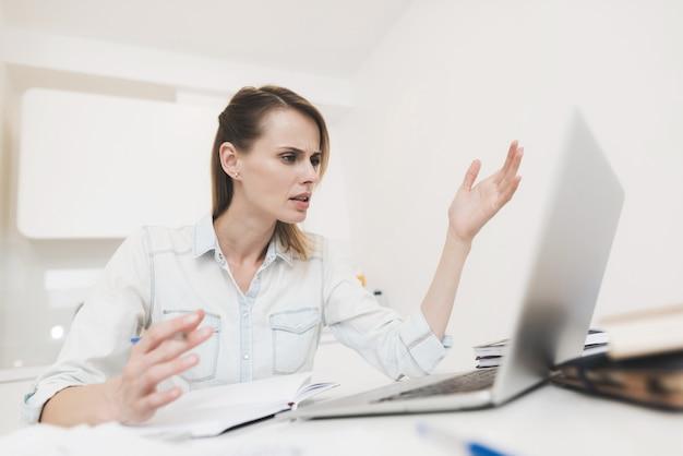 Uma mulher trabalha em casa ela trabalha em um laptop