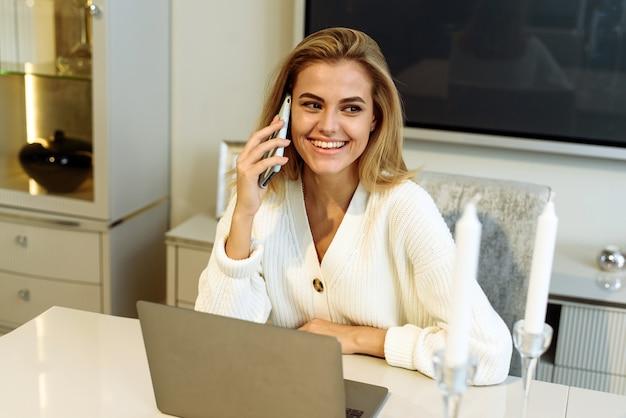 Uma mulher trabalha em casa em um laptop e fala ao telefone com um parceiro de negócios ou chefe.