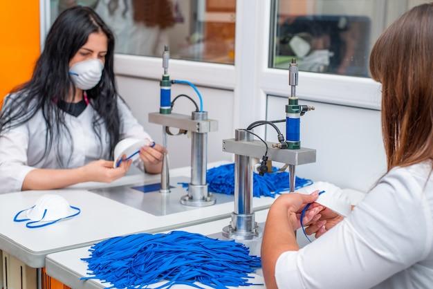 Uma mulher trabalha em uma máquina para a fabricação de máscaras médicas com nanofibras e laços de solda com ultrassom.