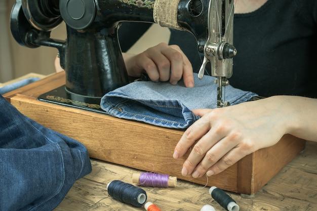 Uma mulher trabalha em uma velha máquina de costura.