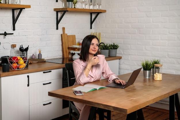 Uma mulher trabalha no escritório, remotamente de casa, na cozinha, sentada diante do computador. ensino à distância, educação online e trabalho. aluna se prepara para os exames.